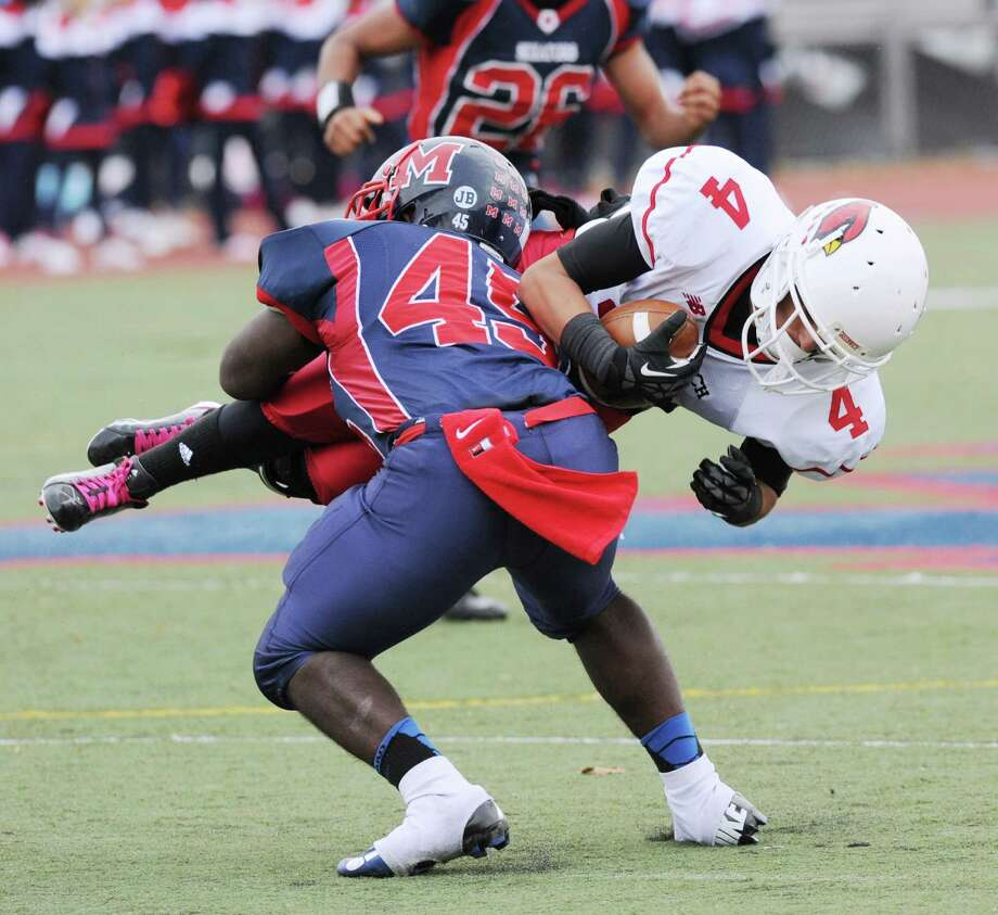 Greenwich receiver Jose Melo # 4 gets  dives while being tackled by Danny O'Brien # 45 of Brien McMahon during the high School football game between Brien McMahon and Greenwich at Brien McMahon High School in Norwalk, Saturday afternoon, Nov. 10, 2012. Photo: Bob Luckey / Greenwich Time