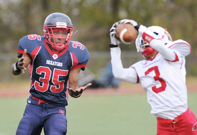 At left, receiver Allan Leonard # 35 of Brien McMahon has a surprised look on his face as Austin Longi # 3 of Greenwich intercepts a pass during the first quarter of the high school football game between Brien McMahon and Greenwich at Brien McMahon High School in Norwalk, Saturday afternoon, Nov. 10, 2012. Photo: Bob Luckey / Greenwich Time