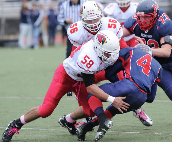 At left, Alex McGee # 58 of Greenwich tackles Trevon Fomey # 4 of Brien McMahon during the high school football game between Brien McMahon and Greenwich at Brien McMahon High School in Norwalk, Saturday afternoon, Nov. 10, 2012. At top left is Jack Wynne # 56 of Greenwich, at right is Andrew Starr # 73 of Brien McMahon. Photo: Bob Luckey / Greenwich Time