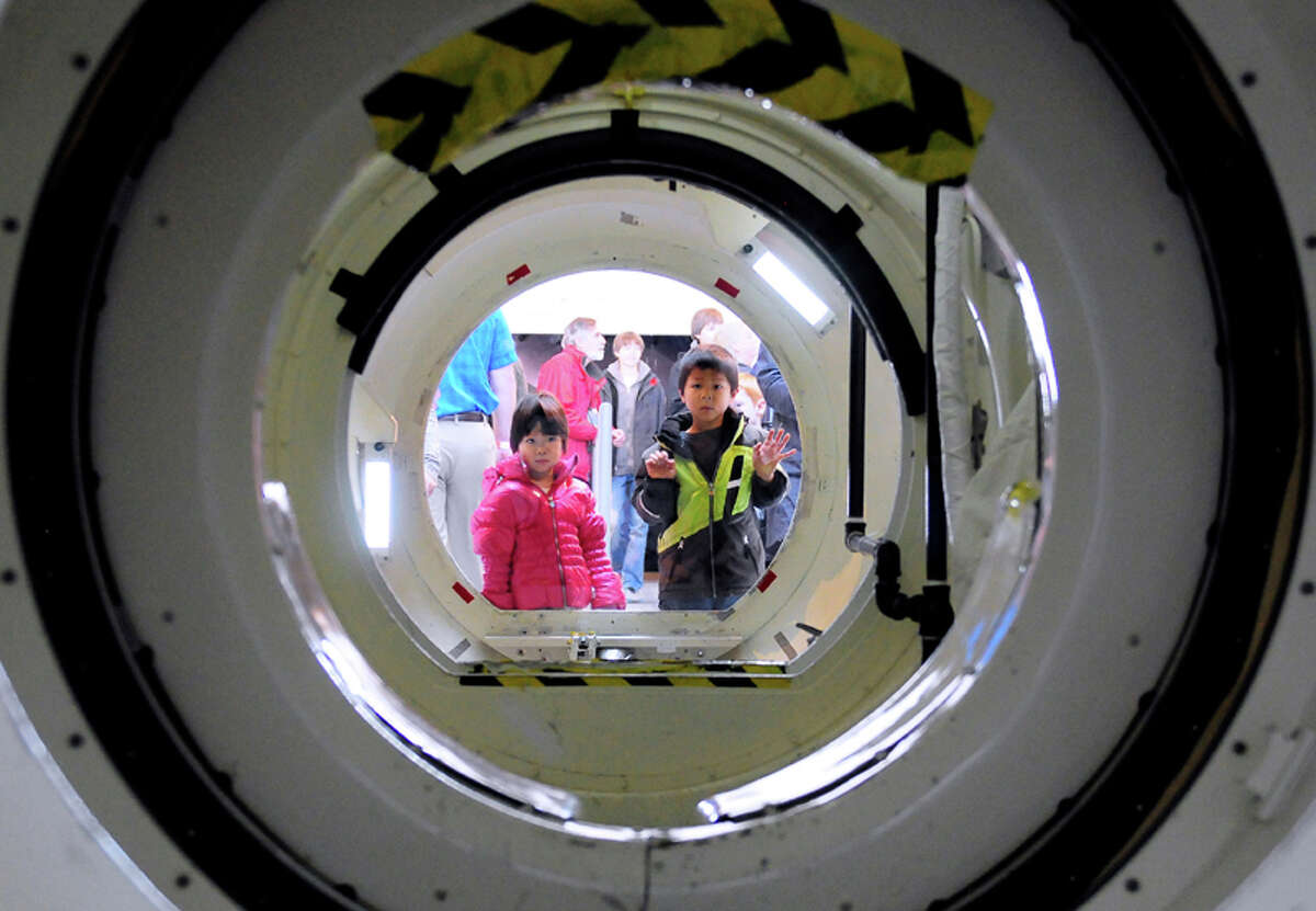 Joyce Lu, 3, and Wyatt Lu, 5, look through the plexiglass of the shuttle's external airlock during the Space Shuttle Trainer Grand Opening at the Museum of Flight's Charles Simonyi Space Gallery on Saturday, November 10, 2012. The public was given its first look inside the one-of-a-kind NASA Space Shuttle Trainer, which each of the space shuttle astronauts trained in before operating the real craft.