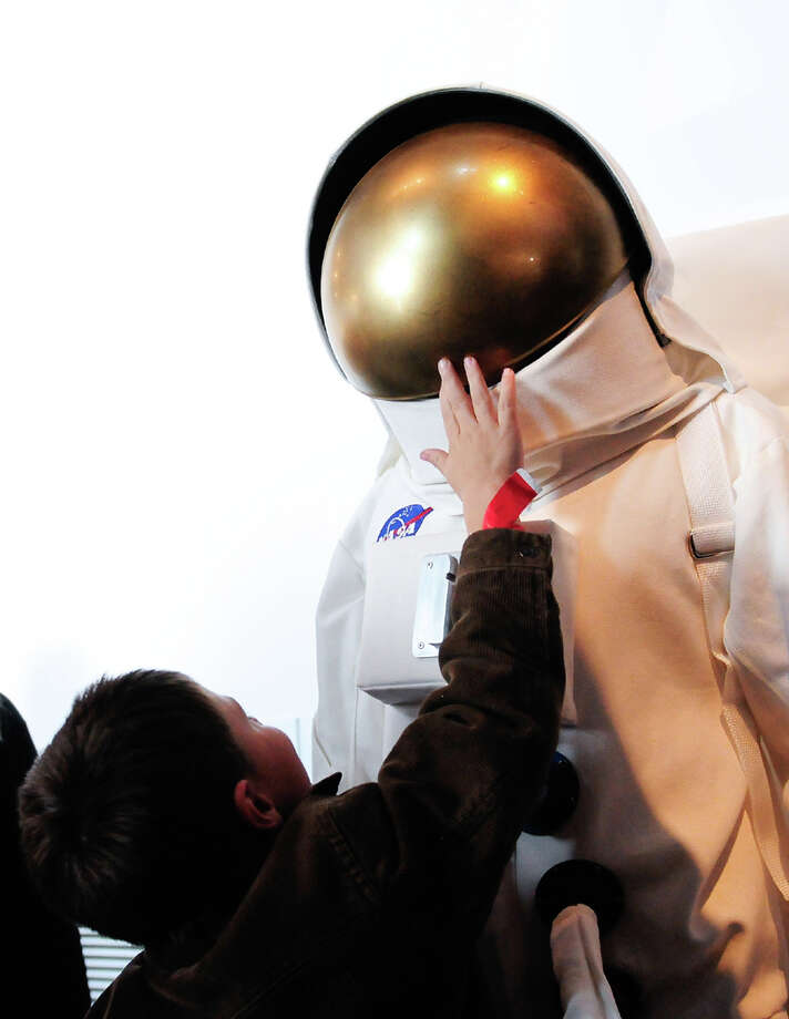 A young boy tries to take a peek behind the visor of a man's space suit during the Space Shuttle Trainer Grand Opening at the Museum of Flight's Charles Simonyi Space Gallery on Saturday, November 10, 2012. The public was given its first look inside the one-of-a-kind NASA Space Shuttle Trainer, which each of the space shuttle astronauts trained in before operating the real craft. Photo: LINDSEY WASSON / SEATTLEPI.COM
