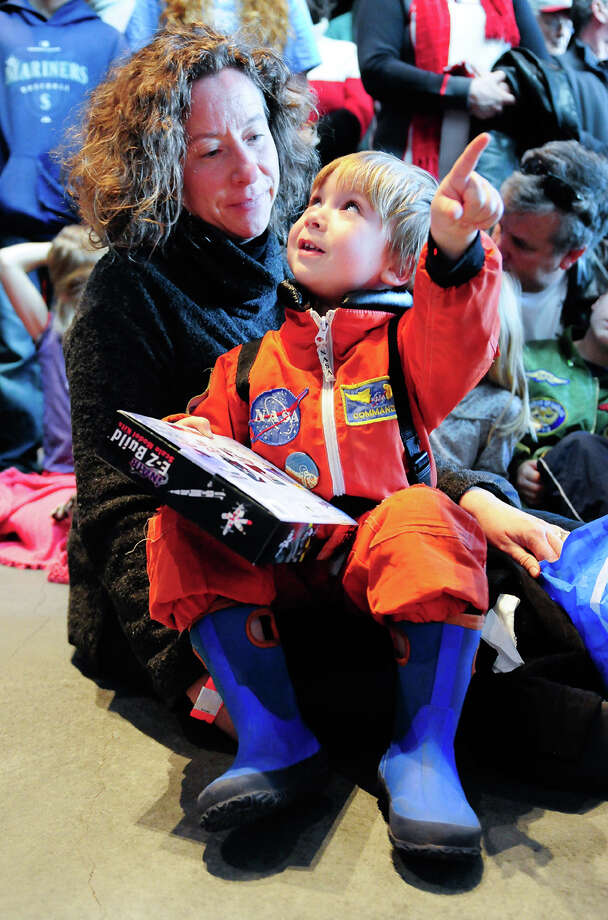 """Dressed in a space suit, Owen Bull, 3 1/2, points at the """"real"""" version of his model Trainer as his mother Lisabeth Bull looks on during the Space Shuttle Trainer Grand Opening at the Museum of Flight's Charles Simonyi Space Gallery on Saturday, November 10, 2012. The public was given its first look inside the one-of-a-kind NASA Space Shuttle Trainer, which each of the space shuttle astronauts trained in before operating the real craft. Photo: LINDSEY WASSON / SEATTLEPI.COM"""