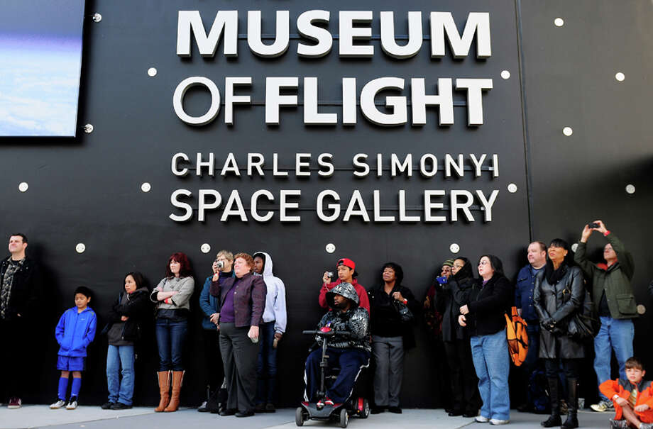 Spectators take photos as the Garfield High School Band plays before the Space Shuttle Trainer Grand Opening at the Museum of Flight's Charles Simonyi Space Gallery on Saturday, November 10, 2012. The public was given its first look inside the one-of-a-kind NASA Space Shuttle Trainer, which each of the space shuttle astronauts trained in before operating the real craft. Photo: LINDSEY WASSON / SEATTLEPI.COM