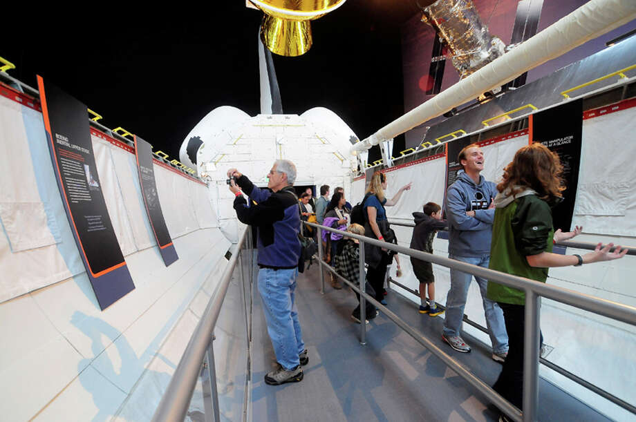 Visitors take photos as they walk through the Space Shuttle Trainer during its Grand Opening at the Museum of Flight's Charles Simonyi Space Gallery on Saturday, November 10, 2012. The public was given its first look inside the one-of-a-kind NASA Space Shuttle Trainer, which each of the space shuttle astronauts trained in before operating the real craft. Photo: LINDSEY WASSON / SEATTLEPI.COM