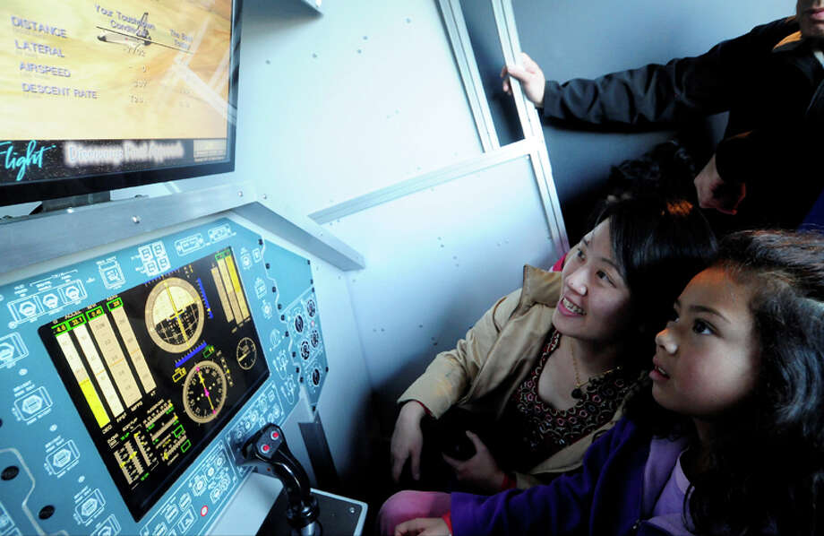 Violet Hatab watches as her daughter Sara, 8, tries her hand at a simulation landing game during the Space Shuttle Trainer Grand Opening at the Museum of Flight's Charles Simonyi Space Gallery on Saturday, November 10, 2012. The public was given its first look inside the one-of-a-kind NASA Space Shuttle Trainer, which each of the space shuttle astronauts trained in before operating the real craft. Photo: LINDSEY WASSON / SEATTLEPI.COM