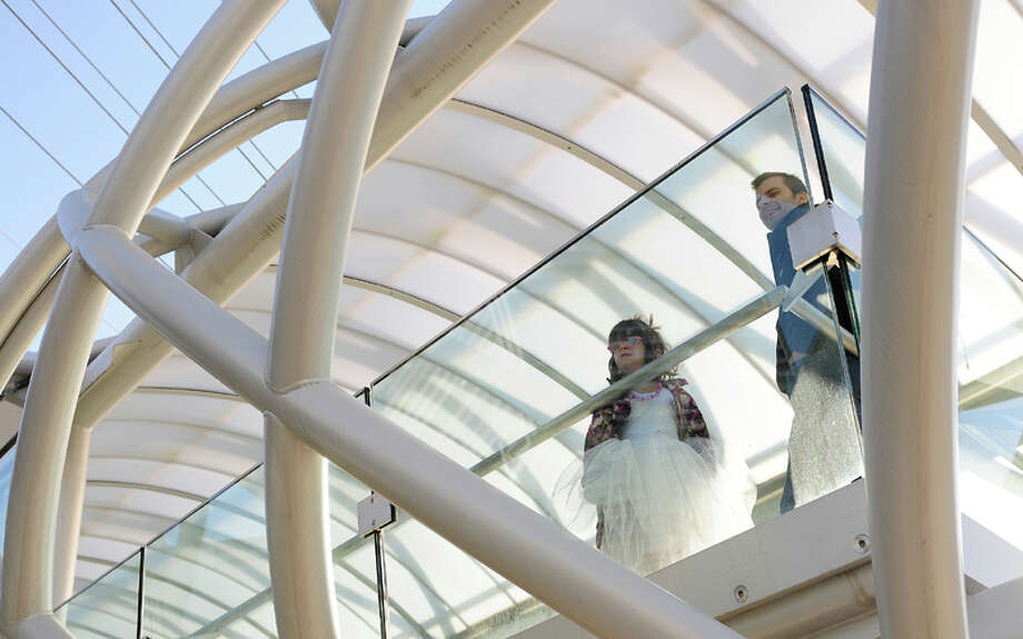 A young girl and her father watch the festivities from the skybridge over the Museum of Flight's Charles Simonyi Space Gallery on Saturday, November 10, 2012. The public was given its first look inside the one-of-a-kind NASA Space Shuttle Trainer, which each of the space shuttle astronauts trained in before operating the real craft. Photo: LINDSEY WASSON / SEATTLEPI.COM
