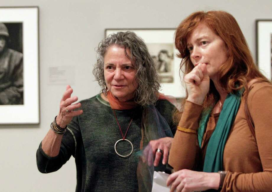 Photographers Gay Block, left, and Heidi Bradner, right, talk together  in the exhibit WAR/PHOTOGRAPHY: Images of Armed Conflict and Its Aftermath at The Museum of Fine Arts, Houston,1001 Bissonnet, Saturday, Nov. 10, 2012, in Houston.  Both have work displayed in the exhibit. Photo: Melissa Phillip, Houston Chronicle / © 2012 Houston Chronicle