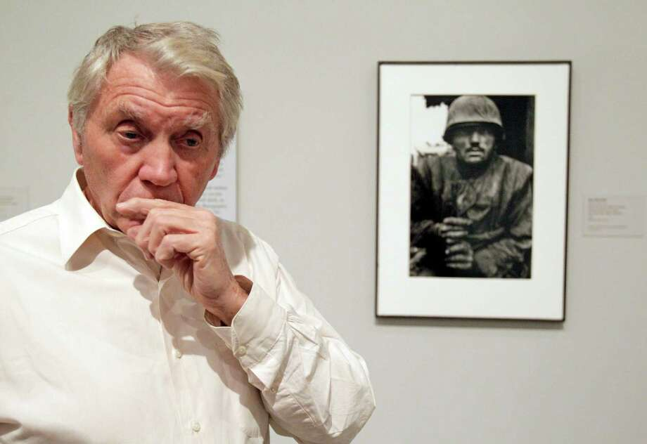 Photographer Don McCullin talks about his work displayed in the exhibit WAR/PHOTOGRAPHY: Images of Armed Conflict and Its Aftermath pose for photos at MFAH, 1001 Bissonnet, Saturday, Nov. 10, 2012, in Houston.  He is standing in front of his 1968 photo of a shell-socker soldier awaiting transportation away from the front line in Hue, Vietnam. Photo: Melissa Phillip, Houston Chronicle / © 2012 Houston Chronicle