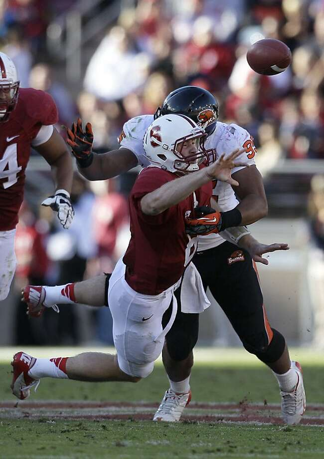 Stanford quarterback Kevin Hogan (8) is hit by Oregon State defensive end Scott Crichton (95) as he throws the ball to running back Stepfan Taylor (33) for a 40-yard touchdown during the third quarter of an NCAA college football game in Stanford, Calif., Saturday, Nov. 10, 2012. (AP Photo/Jeff Chiu) Photo: Jeff Chiu, Associated Press