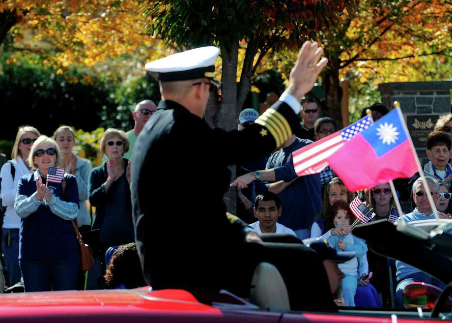 Crowds wave to Navy Capt. Jim Minta as he participates in the 31st annual Veterans Day Parade in downtown Atlanta, Saturday, Nov. 10, 2012. (AP Photo/David Tulis) Photo: David Tulis