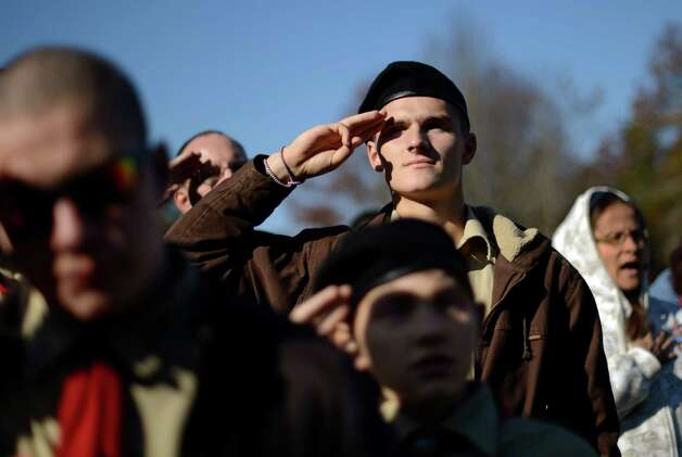 Boy Scout Michael Demanche, of Mashpee, Mass., salutes the flag during a ceremony held at the National Cemetery in Bourne, Mass., Saturday, Nov. 10, 2012. Following the ceremony, Demanche joined hundreds of volunteers in placing thousands of U.S. flags at the graves of deceased veterans in advance of Veterans Day. (AP Photo/Gretchen Ertl) Photo: Gretchen Ertl