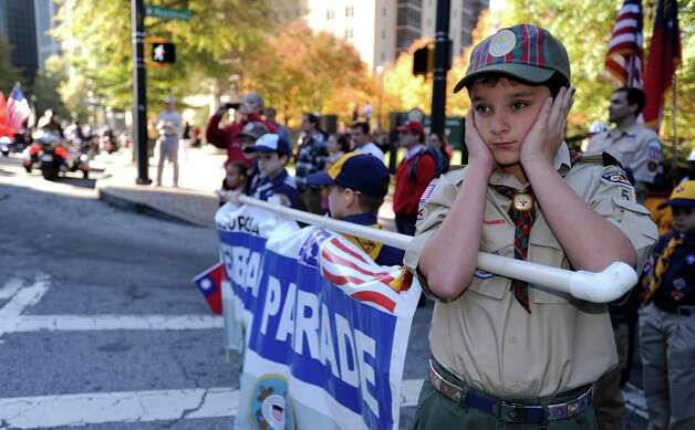 Cub Scout Ethan Jennings covers his ears as motorcycles roar by to start the 31st annual Veterans Day Parade through downtown Atlanta, Saturday, Nov. 10, 2012. (AP Photo/David Tulis) Photo: David Tulis