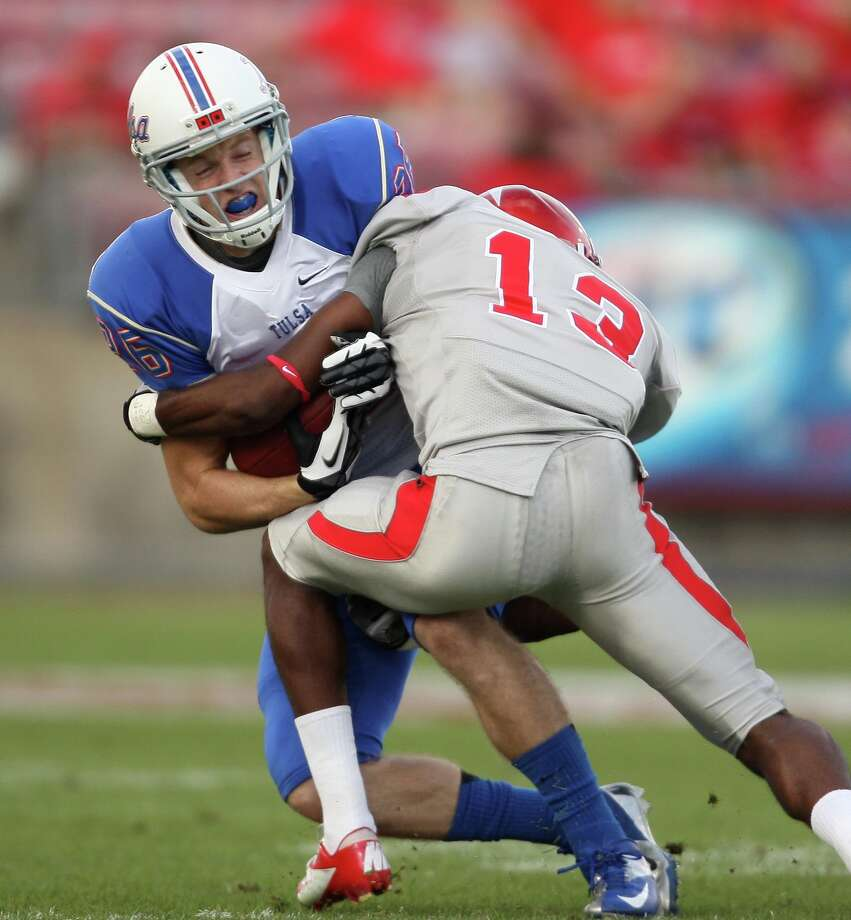 University of Tulsa 's Dexter McCoil (26) is tackled by University of Houston's Thomas Bates during the first half of a college football game, Saturday, November 10, 2012 at Robertson Stadium in Houston, TX. Photo: Eric Christian Smith, For The Chronicle