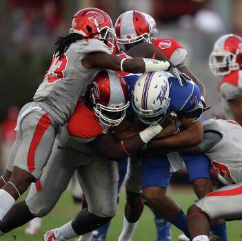 University of Tulsa quarterback Cody Green (7) is tackled for a loss by a wall oh University of Houston defenders during the first half of a college football game, Saturday, November 10, 2012 at Robertson Stadium in Houston, TX. Photo: Eric Christian Smith, For The Chronicle
