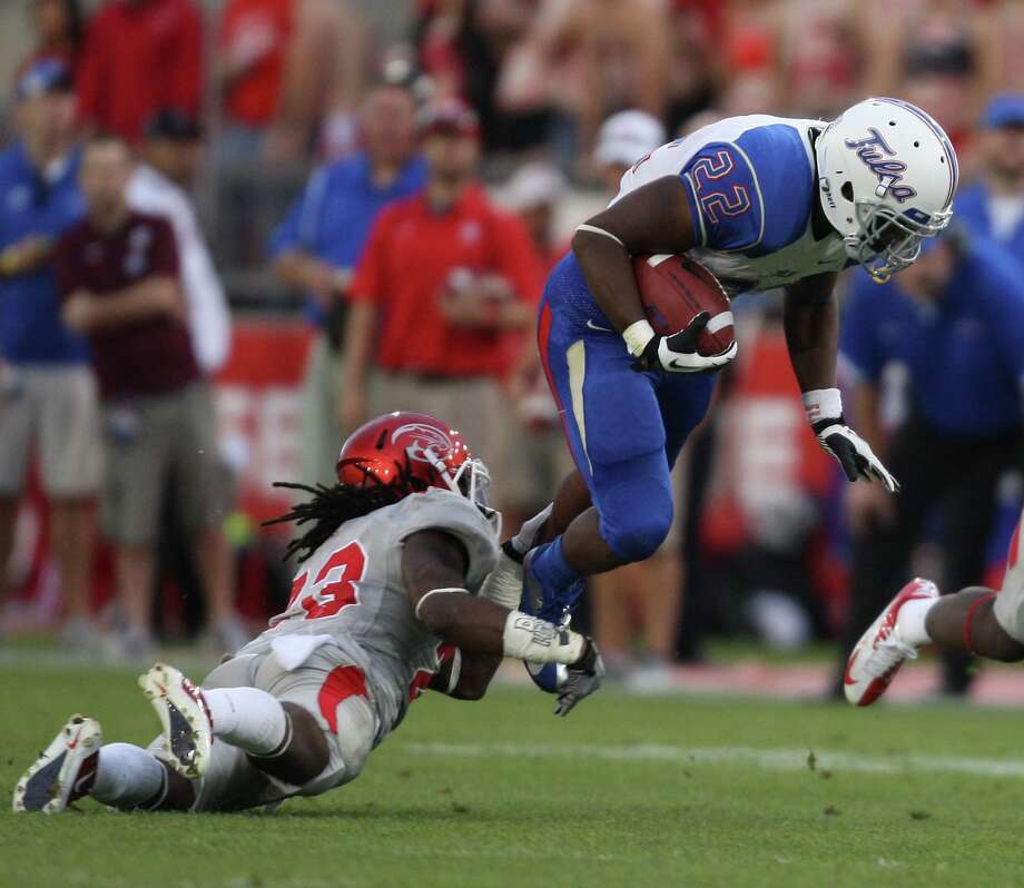 University of Tulsa running back Trey Watts is tackled by University of Houston defensive back Trevon Stewart during the first half of a college football game, Saturday, November 10, 2012 at Robertson Stadium in Houston, TX. Photo: Eric Christian Smith, For The Chronicle