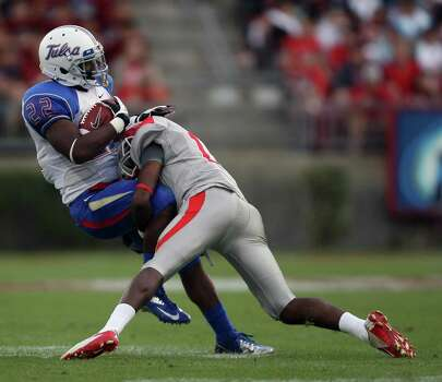 University of Tulsa tailback Trey Watts (22) is tackled by University of Houston defensive back Thomas Bates during the first half of a college football game, Saturday, November 10, 2012 at Robertson Stadium in Houston, TX. Photo: Eric Christian Smith, For The Chronicle