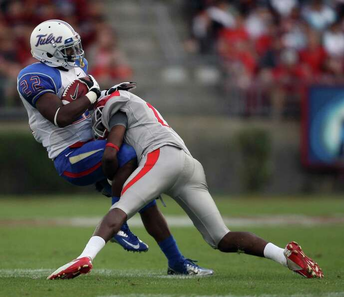 University of Tulsa tailback Trey Watts (22) is tackled by University of Houston defensive back Thom