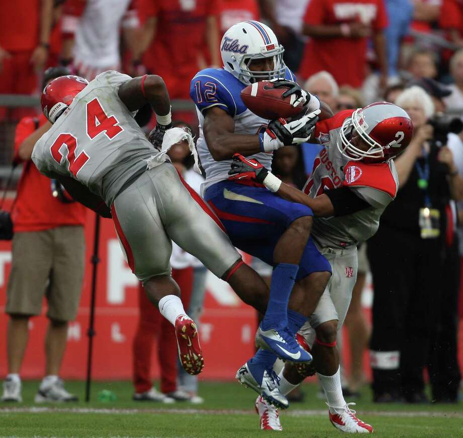 University of Tulsa wide receiver Jordan James (12) makes a reception while University of Houston's Kent Brooks (24) and Zach McMillian defend during the first half of a college football game, Saturday, November 10, 2012 at Robertson Stadium in Houston, TX. Photo: Eric Christian Smith, For The Chronicle