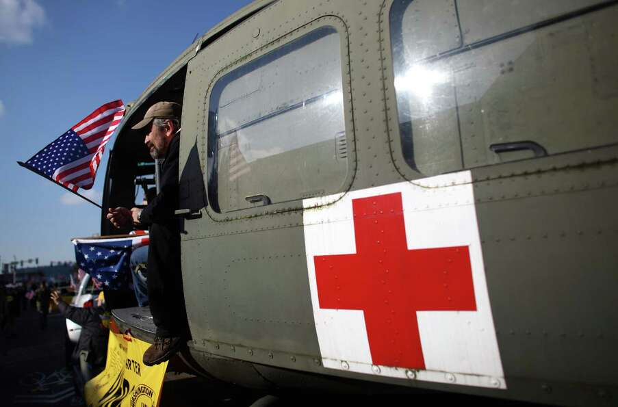 John Salm, who was a U.S. Navy corpsman, rides in a helicopter during the Auburn Veterans Day Parade