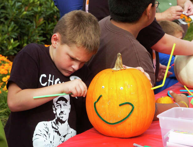 Corey Beaumont, 8, of Lumberton concentrates on decorating his pumpkin Saturday at Shangri La Botanical Gardens' Autumn Fair. The fair featured a scarecrow exhibition, wildlife presentations and children's games. Photo: Sarah Moore