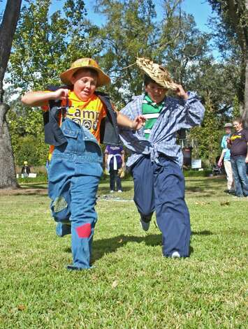 "Louisiana residents Colby Hill and Edwin Hernandez, both 11, compete Saturday in the ""Scarecrow Dress-N-Dash"" race, one of the children's activities at Shangri La Botantical Gardens' Autumn Fair. Photo: Sarah Moore"
