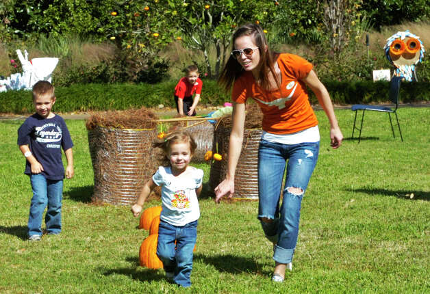 Lauren Wright, 3, gets a hand on the obstacle course from Aunt Haley Folk, 21, of Beaumont as Landon Wright, 6, and Devin Terrell, 5, give encouragement. The family group was enjoying the afternoon at Shangri La Botanical Gardens during its Autumn Fair on Saturday. Photo: Sarah Moore