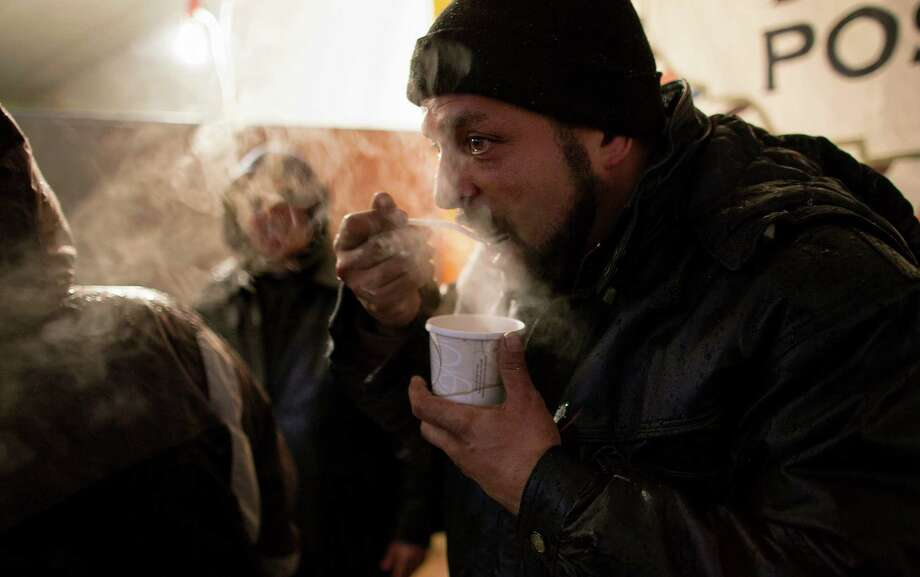 In this Wednesday, Nov. 7, 2012 photo, Benny Roman, volunteer and 30-year resident of Rockaway Park, in the Queens borough of New York, warms up as he eats soup at an outreach center called Yana (You are Never Alone) where members of Occupy Sandy are coordinating with YANA. On this cold and snowy day, volunteers stayed into the night, offering food, clothing and blankets to help those who may have stayed behind or can't leave the devastated area in the wake of Superstorm Sandy.  (AP Photo/Craig Ruttle) Photo: Craig Ruttle, Associated Press / FR61802 AP