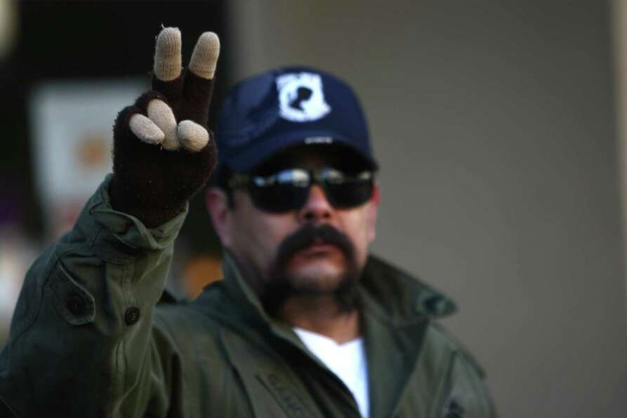 A spectator holds up a peace sign during the Auburn Veterans Day Parade. The group