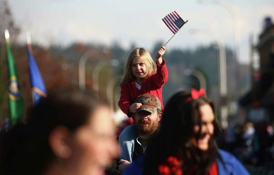 A young participant waves a flag in the Auburn Veterans Day Parade. Photo: JOSHUA TRUJILLO / SEATTLEPI.COM