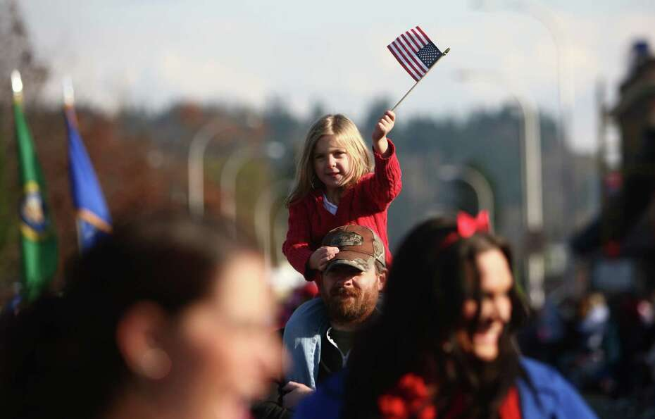 A young participant waves a flag in the Auburn Veterans Day Parade.
