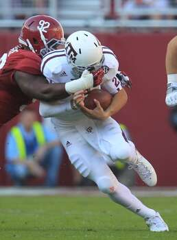 Texas A&M quarterback Johnny Manziel (2) is brought down by his face mask by Alabama defensive lineman Damion Square (92) during the first quarter of a college football game at Bryant-Denny Stadium, Saturday, Nov. 10, 2012, in Tuscaloosa.  ( Karen Warren / Houston Chronicle ) (Houston Chronicle)