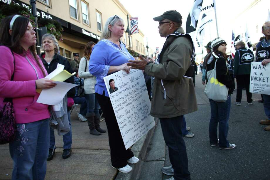 "Cheyenne St. Jacque, who came to the parade with a sign that said her military veteran husband recently committed suicide, is addressed by members of the group ""Veterans For Peace"" during the Auburn Veterans Day Parade. She said that she came to the parade as a cry out for help because a bank may take the home she shares with her special needs daughter. The group ""Veterans For Peace"" was initially denied entry into the parade by the City of Auburn until a judge ordered the city to allow the group to march on free speech grounds. Photo: JOSHUA TRUJILLO / SEATTLEPI.COM"