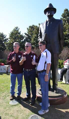 Texas A&M fans David Cunningham, left, Daryl Heath, center and Kyle Walker get their photos taken in front of the Bear Bryant statue before the start of a college football game at Bryant-Denny Stadium, Saturday, Nov. 10, 2012, in Tuscaloosa.  ( Karen Warren / Houston Chronicle ) (Houston Chronicle)