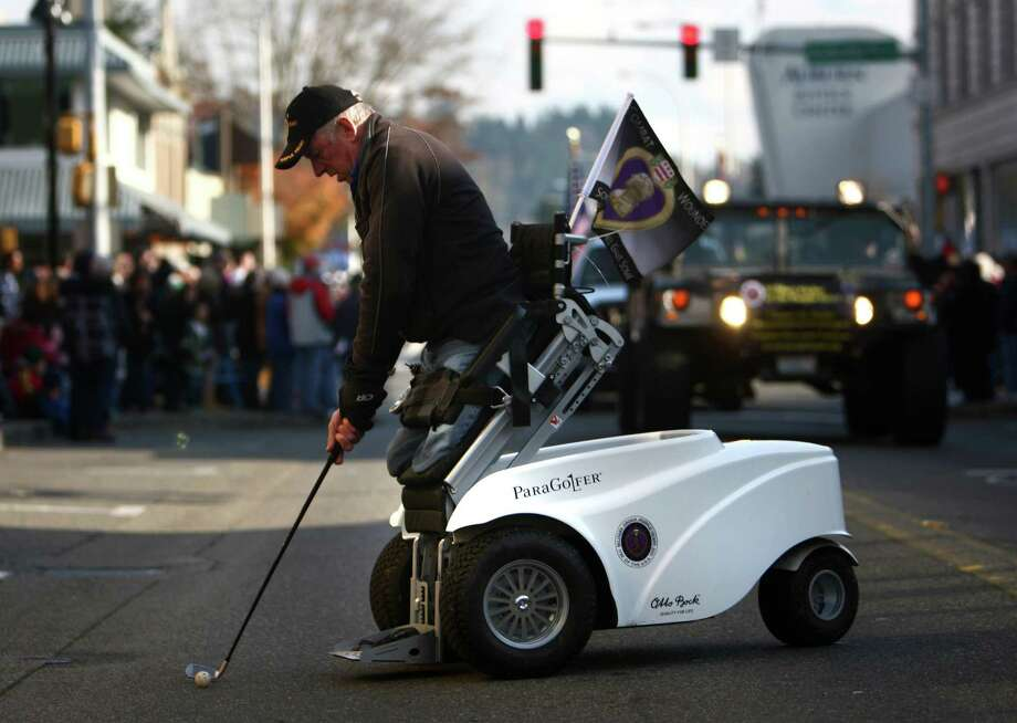 Vietnam War Army veteran Jim Martinson, who was awarded a Purple Heart during the war, hits a golf ball with a ParaGolfer chair as he rides in the Auburn Veterans Day Parade. Photo: JOSHUA TRUJILLO / SEATTLEPI.COM