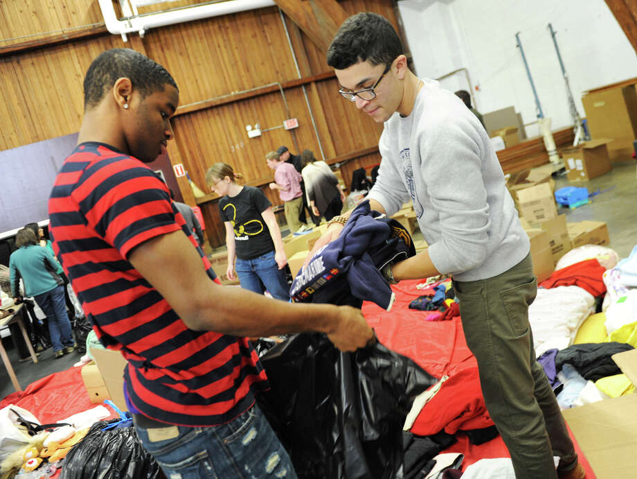 Freshmen Adrian Morgan, left, and Raymond Farmer put sweatshirts into garbage bags as Union students and staff sort, label and load supplies donated by the campus community for victims of Sandy onto a van Friday, Nov. 9, 2012 in Schenectady, N.Y.  (Lori Van Buren / Times Union) Photo: Lori Van Buren