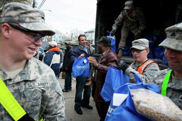 New York Governor Andrew Cuomo assists the National Guard unload a truck of supplies in the Far Rockaways section of the Queens borough of New York, Saturday, Nov. 10, 2012.  Despite power returning to many neighborhoods in the metropolitan area, residents of the Far Rockaways continue to live without power and heat due to damage caused by Superstorm Sandy.(AP Photo/John Minchillo) Photo: John Minchillo