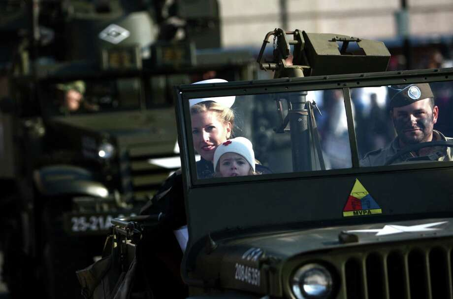Participants ride in military vehicles during the Auburn Veterans Day Parade. Photo: JOSHUA TRUJILLO / SEATTLEPI.COM