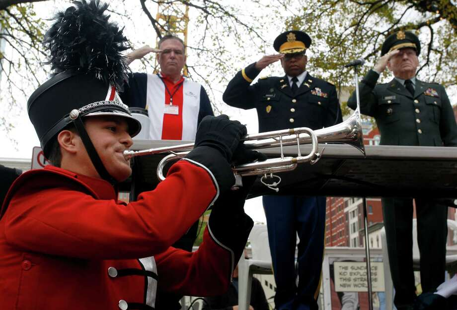 "Dakota Cuttrell, of Southwest High School Marching Band, plays ""Taps""  as, from left, Roland Paquette, Col. Richard Crossley, and Col. Russel Bracy salute during the Veterans Day Parade in Downtown Fort Worth, Texas on Saturday. Nov. 10, 2012. Photo: Richard W. Rodriguez, Associated Press / The Fort Worth Star-Telegram"