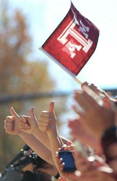 Texas A&M fans cheer as the team arrives on their buses before the start of a college football game