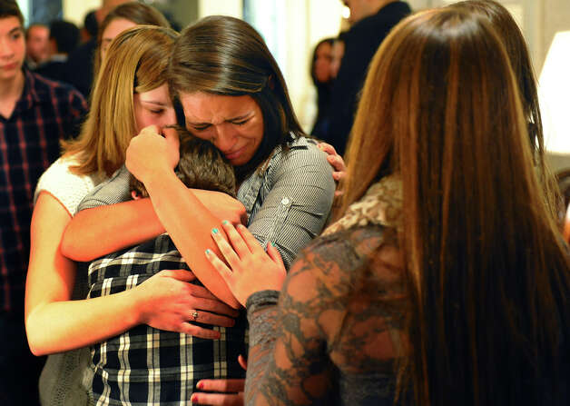Billy Grzywacz, 11, is comforted by Jocelyn Grzywacz and Nicole Burr, at left, after a memorial service for their cousin Jet Krumwiede at Smith & Sefcik Funeral Home in Milford, Conn. on Saturday November 10, 2012. Krumwiede went missing in advance of Superstorm Sandy while kayaking with a friend. Photo: Christian Abraham / Connecticut Post