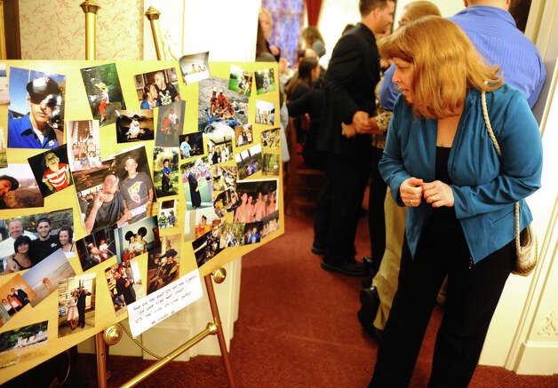Jean Gardino looks at a collage of photos during a memorial service for Milford resident Jet Krumwiede at Smith & Sefcik Funeral Home in Milford, Conn. on Saturday November 10, 2012. Krumwiede went missing in advance of Superstorm Sandy while kayaking with a friend. Photo: Christian Abraham / Connecticut Post