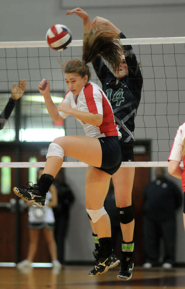 Clear Falls sophomore outside hitter Alyssa Enneking, from right, tips the ball past Clear Lake senior setter Sam Volk during their Region III 5A Regional Final at the M.O. Campbell Educational Center on Saturday. Photo by Jerry Baker Photo: Jerry Baker, For The Chronicle