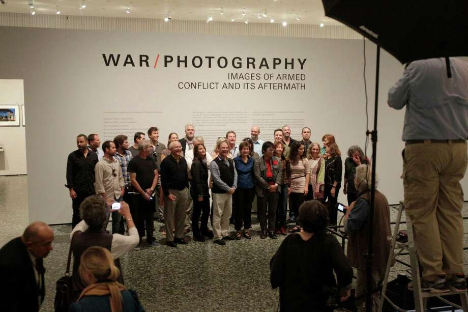 "Some of the photographers whose work is displayed in ""WAR/PHOTOGRAPHY: Images of Armed Conflict and Its Aftermath,"" gather Saturday at the museum. Photo: Melissa Phillip, Staff / © 2012 Houston Chronicle"