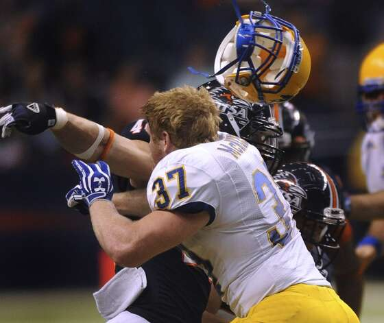 McNeese State fullback Dylan Long loses his helmet as he blocks UTSA linebacker Steven Kurfehs during college football action in the Alamodome on Saturday, Nov. 10, 2012. (San Antonio Express-News)