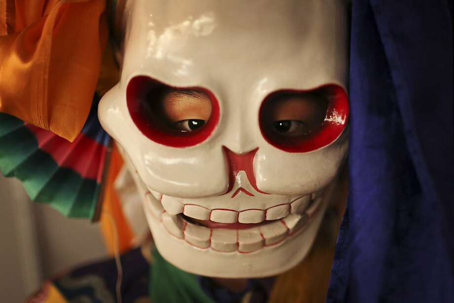 "A Tibetan Buddhist monk from the Sherbling Monastery in the Indian state of Himachal Pradesh, wears a mask as he waits before performing a ""bone dance"" at the closing of the Delhi International Arts Festival in New Delhi, India, Saturday,Nov. 10, 2012. The dance, which is usually part of a prayer ritual, is performed for entertainment purposes only. (AP Photo/Kevin Frayer) Photo: Kevin Frayer, Associated Press"