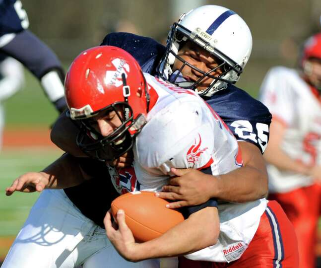 Rensselaer's Seth Butler (25), right, tackles Moriah's Cameron Wright (32) during their Class D regi