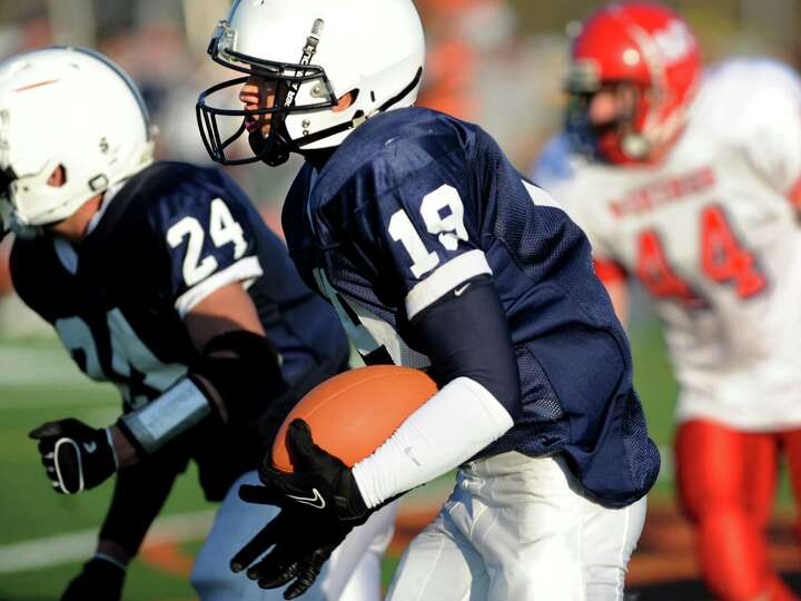 Rensselaer's Brandon Butler (19), center, runs after intercepting a pass during their Class D region