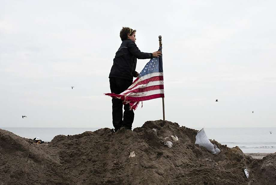 Matt Daly, 12, of Connecticut, places a U.S. flag atop a pile of sand removed from streets in the Rockaways, Saturday, Nov. 10, 2012, in the Queens borough of New York. Despite power returning to many neighborhoods in the metropolitan area after Superstorm Sandy crashed into the Eastern Seaboard, many residents of the Rockaways continue to live without power and heat due to damage caused by Superstorm Sandy. (AP Photo/John Minchillo) Photo: John Minchillo, Associated Press