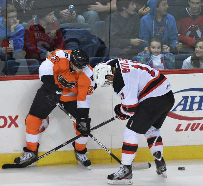 Adirondack's #22 Eric Wellwood, left, and Devils' #11 Bobby Butler during Saturday night's game at t