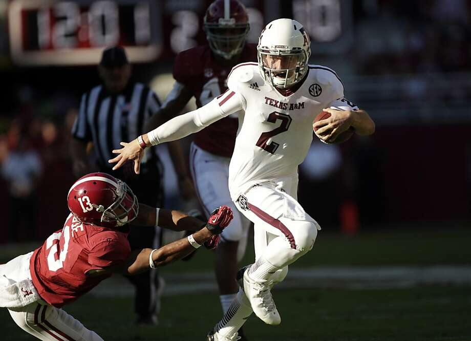 Texas A&M quarterback Johnny Manziel (2) runs through the tackle of Alabama defensive back Deion Belue (13) during the first half of an NCAA college football game at Bryant-Denny Stadium in Tuscaloosa, Ala., Saturday, Nov. 10, 2012. (AP Photo/Dave Martin) Photo: Dave Martin, Associated Press